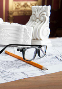 Closeup portrait of spectacles, yellow pencil, design drawing and white stucco moulding, on wooden table over classical interior at studio shot